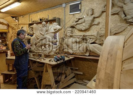 ST. PETERSBURG, RUSSIA - OCTOBER 27, 2016: Wood carver Anatoly Zharov works on wooden decoration of the first Russian ship of the line Poltava reconstructed at the historical shipyard