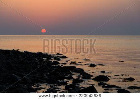 The rocky shore against the setting sun landscape