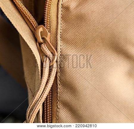 Zipper on backpack closeup, cloth sand color
