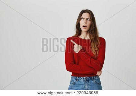 Don't listen to him. Close up portrait of young pretty caucasian female student with brown hair in red jumper and denim jeans pointing on his friend with unsatisfied face expression. Copy space.