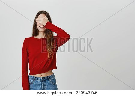 I don't see anything. Close up of funny joyful caucasian girl with long dark hair in stylish clothes smiling with teeth, clothing eyes with hand, waiting for birthday present from friends.