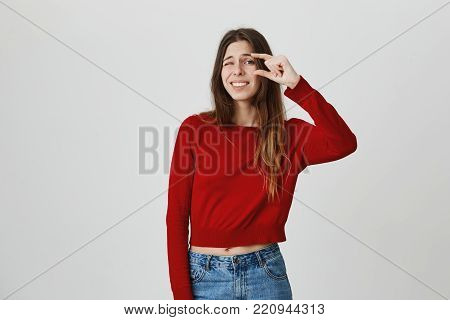 Copy space. Isolated studio portrait of young good-looking caucasian girl with long hair in red sweater and denim jeans gesticulating with hands, showing that this food portion is too small