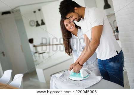 Young happy couple at home doing hosehold chores and ironing