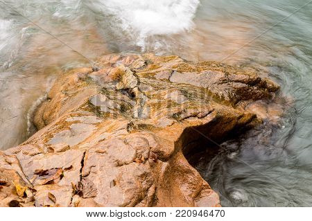 power of nature, time, environment concept. in the course of time this strong and fast moving flow are smoothing down red rough rocks of the stony coast of river