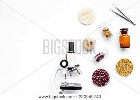 Food safety. Wheat, rice and red beans near microscope on white background top view.