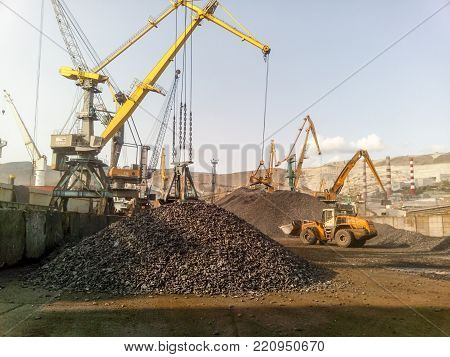 Novorossiysk, Russia - August 20, 2017: Cargo industrial port, port cranes. Loading of anthracite. Transportation of coal. Heap of coal