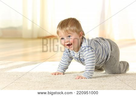 Happy baby crawling and laughing on a carpet at home with a warm light in the background