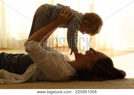 Backlighting side view of a proud mother raising her happy baby lying on a carpet at home