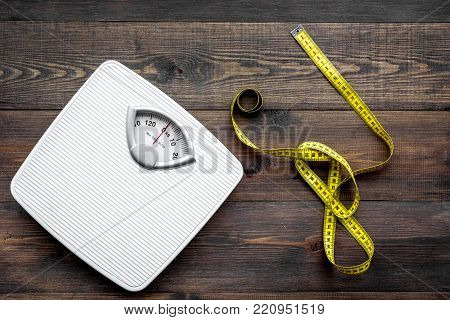 Lose weight concept. Scale and measuring tape on dark wooden background top view.