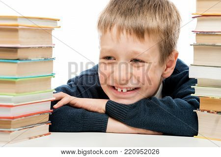 8-year-old Schoolboy Reading A Book At A Table, Portrait Isolated
