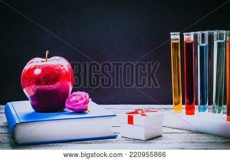 Back to School and Education concept. classroom with book, apple and laboratory chemical test tubes on chalkboard background. school border with copy space
