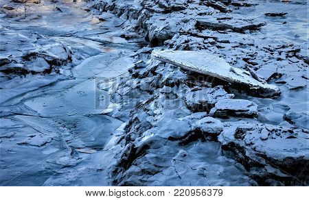 Winter background with frozen ice and ice burgs in nature lining a river bank,textured by nature
