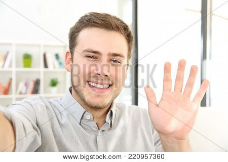 Man waving on a video call sitting on a sofa at home