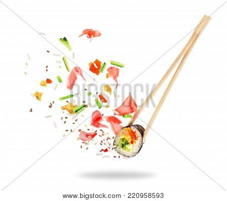 Piece of sushi sandwiched between chopsticks, isolated on white background