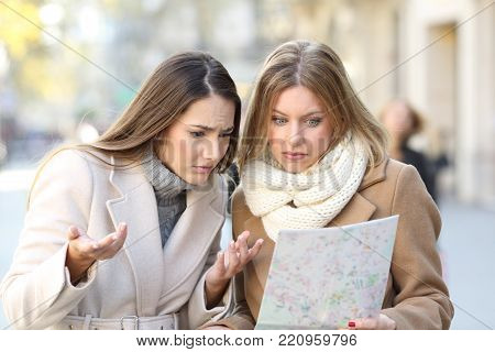 Front view portrait of two lost tourists women searching location in a guide on the street in winter holidays