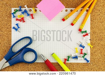Empty white sheet of paper, wrested from notepad for your text. There are around it color pencils, pen, scissor, yellow highlighter and block of pink sticknotes.The sheet is orientation  by the horizon.