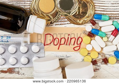 Drugs and undeserved medals. Doping lettering beside tablets, capsules and bottles. Sports and crime.
