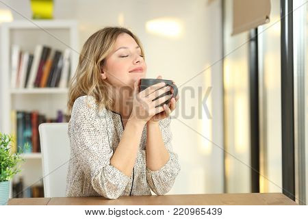 Portrait of a woman breathing and holding a coffee mug at home