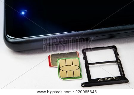 SIM cards and a tray for them near the phone with a shallow depth of field