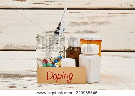 Banned medications and Doping lettering. Pills, bottles and syringe. Unfair play, cheating in sports.