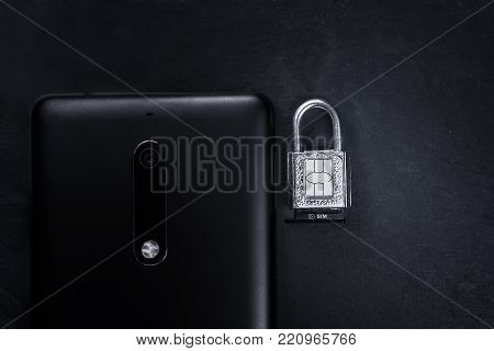 lock and sim card on it next to smartphone on black slate