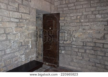 An old open door and a brick wall in a dungeon or in a castle.