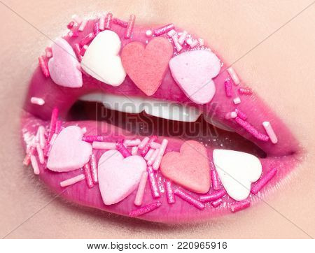 Valentine Hearts sweet makeup. Valentine's Day make-up lips with pink hearts sugar sprinkles. Kiss on the Lips. Makeup. Beauty Sexy Lips with Heart Shape paint. Valentines Day. Beautiful Love Make-up