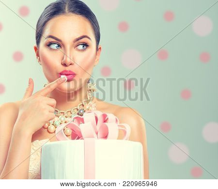 Beauty fashion model girl holding Beautiful Big Cake and tasting it. Funny joyful styled woman with wedding, party or birthday cake on polka dots background. Diet concept. Slimming, weight loss