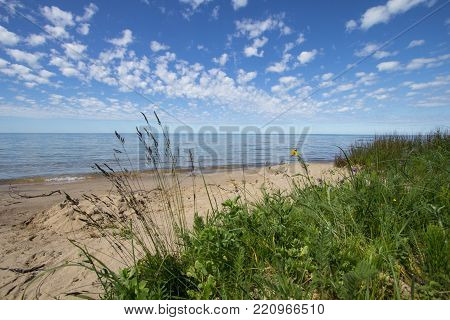 Scenic Sandy Beach Background. Sunny and sandy beach with dune grass in the foreground and a beautiful blue sky at waters horizon. Lake Michigan, Upper Peninsula, USA.