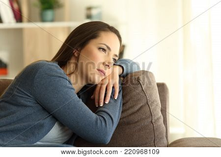 Sad woman looking trough a window sitting on a couch in the living room at home
