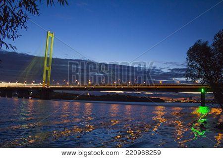 The South bridge at night, Kiev, Ukraine. Bridge at sunset across the Dnieper River. Kiev bridge against the backdrop of a beautiful sunset in Kiev. Bridge in evening sunshine.