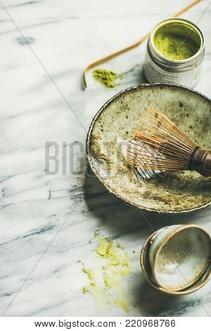 Flat-lay of Japanese tools and bowls for brewing matcha tea. Matcha powder in tin can,