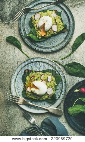 Healthy vegetarian breakfast flat-lay. Whole-grain toasts with avocado, spinach and poached eggs over grey concrete background, top view. Clean eating, diet, gluten-free food concept