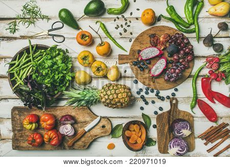 Helathy raw vegan food cooking background. Flat-lay of Fresh fruit, vegetables, greens and superfoods on boards over white wooden table, top view. Clean eating, alkaline diet, vegetarian concept