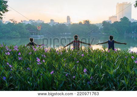 Hanoi, Vietnam - August 21, 2017: Three Women Doing Exercise On Hoan Kiem Lake In The Morning