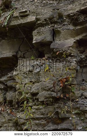 Crumbling shale rock face on the side of the road abstract texture background.