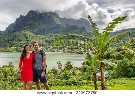 Bora Bora luxury cruise travel vacation tourists couple in front of Mt Otemanu in French Polynesia. Tahiti getaway holiday people visiting the island during cruise excursion tour.