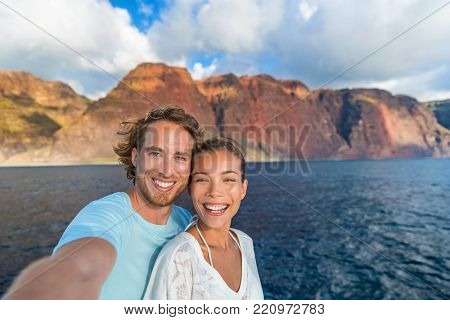 Happy couple tourists on sunset cruise in Na Pali Coast Kauai, Hawaii taking selfie photo with mobile phone app. Smiling Asian woman and Caucasian man taking picture on summer holiday.