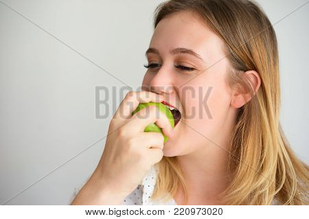 Cheerful young woman enjoying taste of green apple biting it. Positive dental patient eating apple for healthy teeth. Stomatology or oral medicine concept
