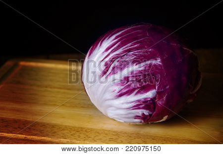Purple And White Head Of Radicchio Lettuce Resting On Wooden Cutting Board