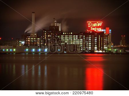 Baltimore, MD--October 13, 2017, time exposure of domino sugar factory and buildings at dawn with reflection of neon sign on harbor