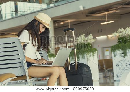 Young woman in airport waiting for air travel using tablet. She is sitting with travel suitcase trolley, in waiting hall of departure lounge in airport.Travel Concept .