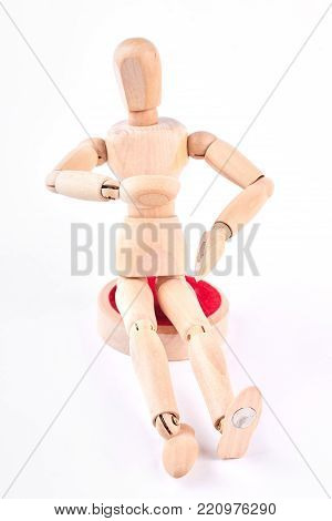 Wooden dummy sitting on white background. Human wooden mannequin touching its stomach. Wooden dummy sitting over white.