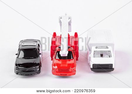 Set of car toys, front view. Police car, fire truck and emergency ambulance car toys on white background.