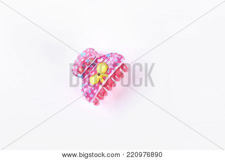 Pink plastic hair clip on white background. Little hair claw with yellow bow isolated on white background. Kids hair accessory.
