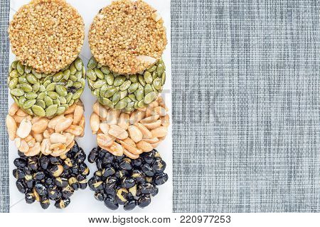 Korean traditional sweet snacks with peanuts, pumpkin seeds, black soybeans and chinese buckwheat. Healthy energy snacks. Top view, horizontal, copy space