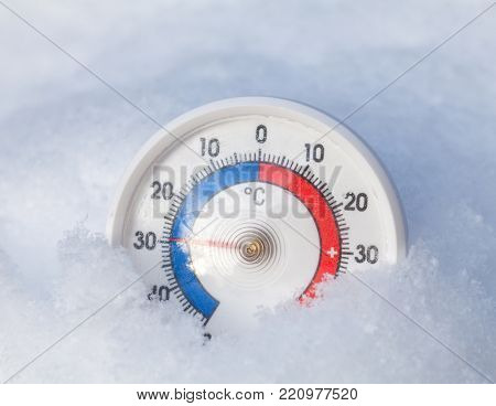 Frozen thermometer with celsius scale in snow showing extreme low sub-zero temperature minus 29 degree a cold winter weather concept