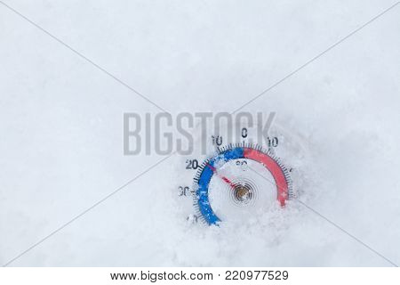 Frozen thermometer with celsius scale in snow showing low sub-zero temperature minus seventeen degree a cold winter weather concept