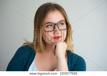 Introspective intelligent young woman deep in thoughts leaning on hand. Pensive attractive student girl in eyeglasses thinking of career. Aspirations concept