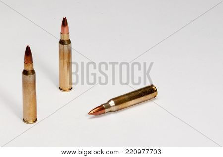 A white background and a three 223 cartridges